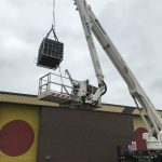Lifting materials with an access platform and boom winich